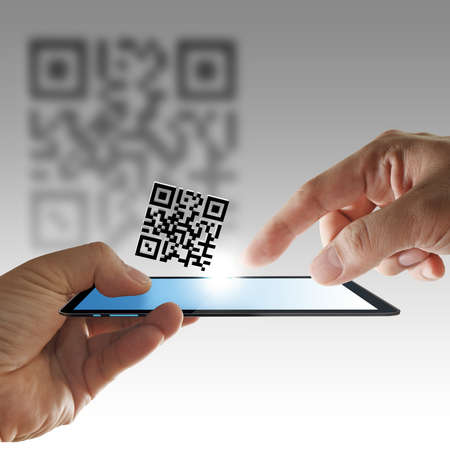 the reader: close up of hand and tablet computer scan Qr code as concept Stock Photo