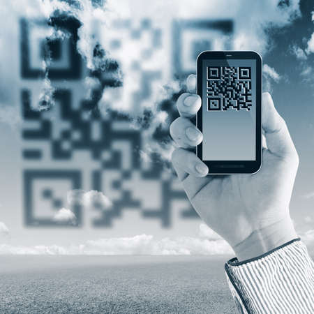 Scanning Qr code with mobile smart phone on sky background photo