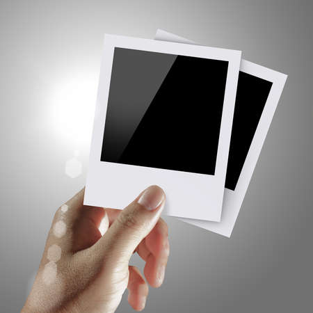 flash light: hand holds blank photos with flash light background