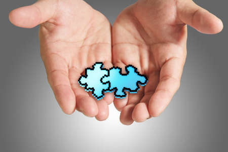 close up of hand holds pixel puzzle icon as concept partnership business photo
