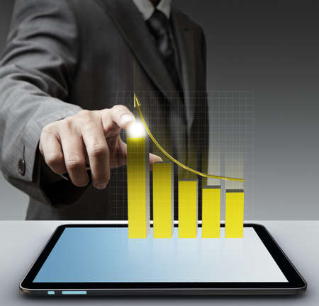 business man hand point to virtual gold graph with tablet computer
