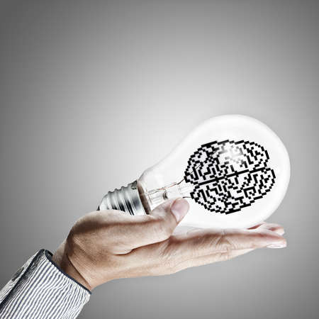 hand shows 3d pixel icon brain in light bulb as concept photo