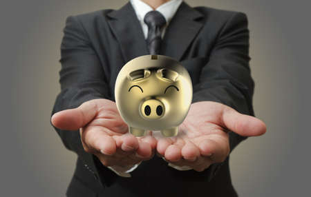 business loans: Businessman shows a piggy bank