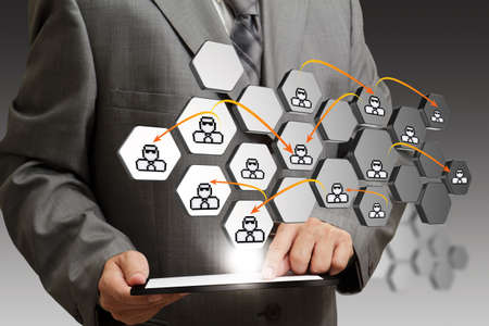 business man hand using tablet computer and abstract icon as social network concept photo
