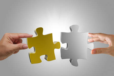 joining hands: gold and silver3d puzzles in hands as concept Stock Photo