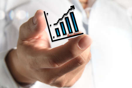 growth in economy: close up of hand holds pixel graph as concept Stock Photo