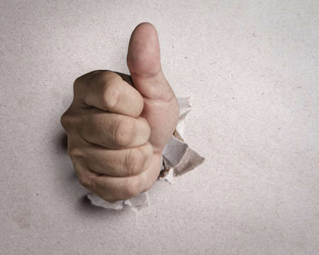 male hand with thumb up breaking through white background photo