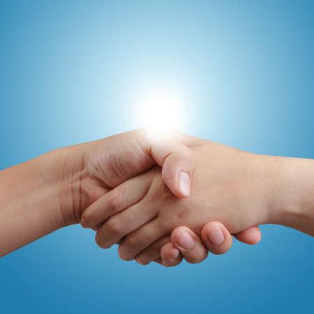 saludo de manos: apret�n de manos y la luz del sol de fondo