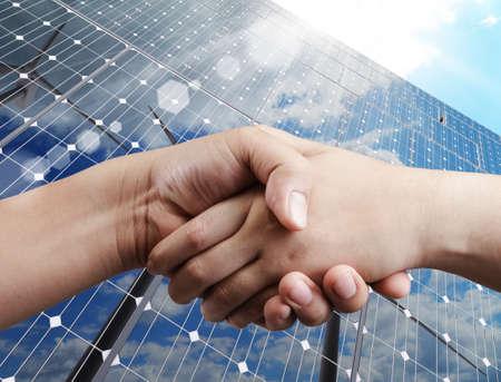 energia solar: apret�n de manos y la luz del sol de fondo