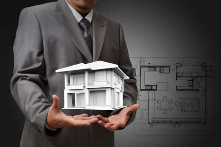 build structure: The house in hands on blue print