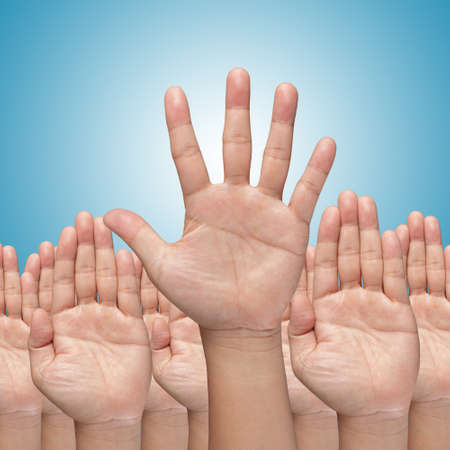 to raise: Many Hands raise high up on blue background