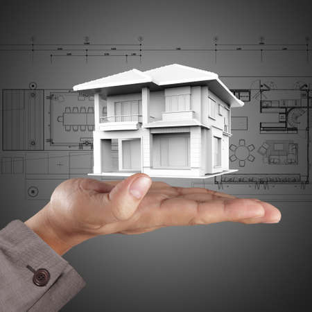 The house in hands on blue print photo