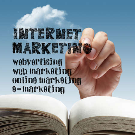 content writing: hand holds a marker in hand writing down the various strategies of Online Internet Marketing. Stock Photo