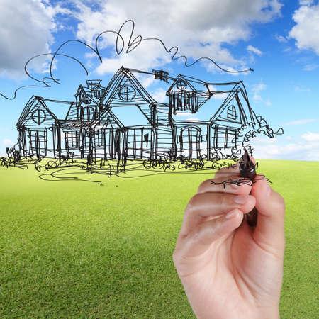 реальный: рука ничья дома против голубого неба и зеленой травы Фото со стока