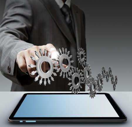 Business man show gear to success from touch screen computer Stock Photo - 15069972