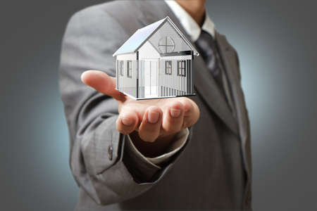 sell house: Business man present  diamond house model Stock Photo