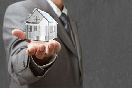 realestate: A small house on businessman hand Stock Photo