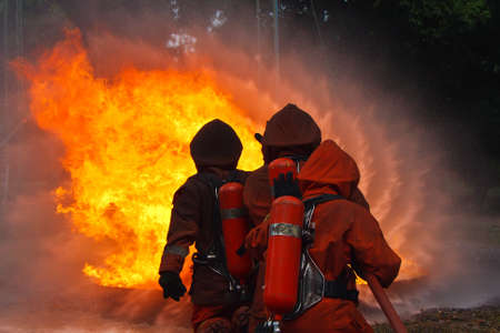 hoses: Firefighters fighting fire during training