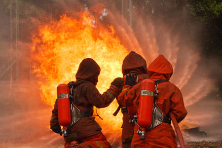 fire hoses: Firefighters fighting fire during training