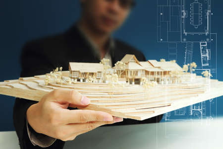 Architect holding house model and show layout plan on touch screen Stock Photo - 16080428