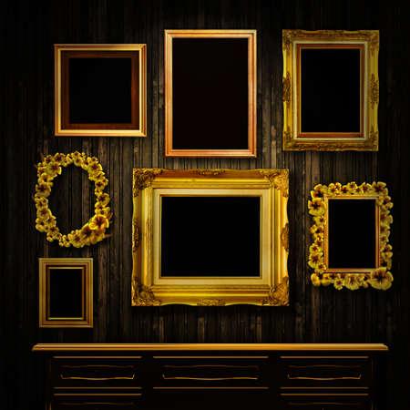 gild: Galleria display - cornici in oro d'epoca e una cassettiera su una parete in legno vecchio