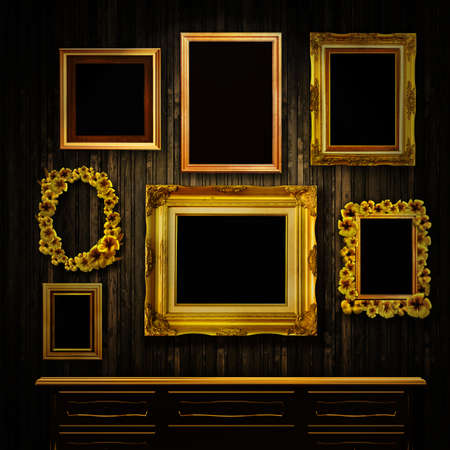Gallery display - vintage gold frames and a chest of drawers on an old timber wall photo