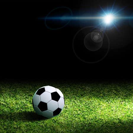 bola: Esfera de futebol na grama de encontro ao fundo preto Banco de Imagens