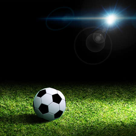 Soccer ball on grass against black background photo