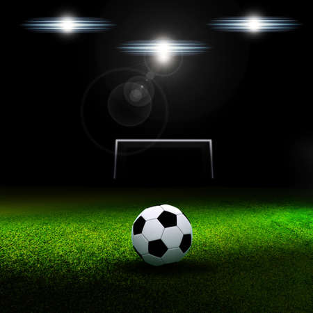 Soccer ball on grass against black background (stadium)