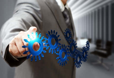 innovation technology: business man hand point cogs icons in board room Stock Photo
