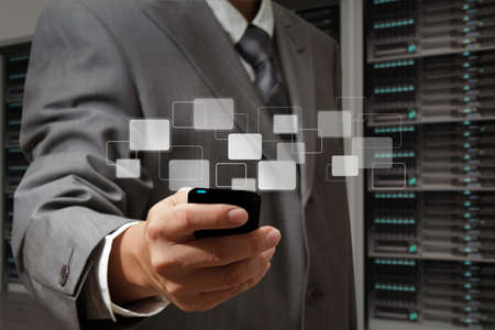 server icon: business man holds touch screen mobile phone in server room