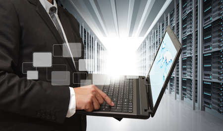 data backup: business man use notebook in server room Stock Photo
