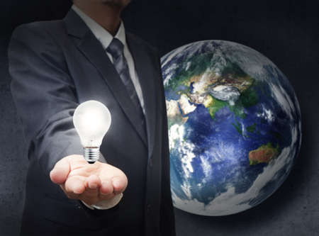 businessman holds light bulb to glowing the earth photo