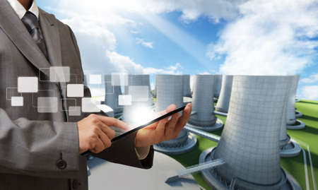 business man hand tablet computer and nuclear power plant background Stock Photo