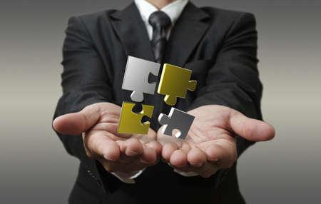 business man shows 3d metallic puzzle as concept Standard-Bild