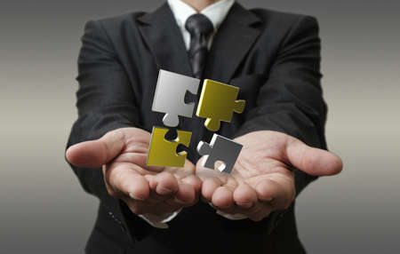 business man shows 3d metallic puzzle as concept Stockfoto