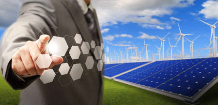 business man hand point virtual buttons and wind turbine and solar farm as concept Archivio Fotografico
