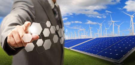 obchodní muž rukou bod virtuální tlačítka a větrné turbíny a solární farmy jako koncept