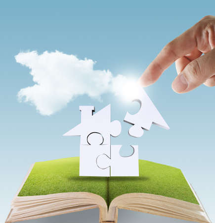 dream house: open book of hand complete puzzle home as concept Stock Photo