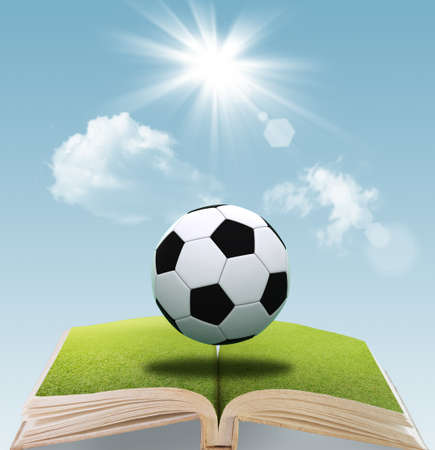 open book of soccer ball on green grass and blue sky background photo