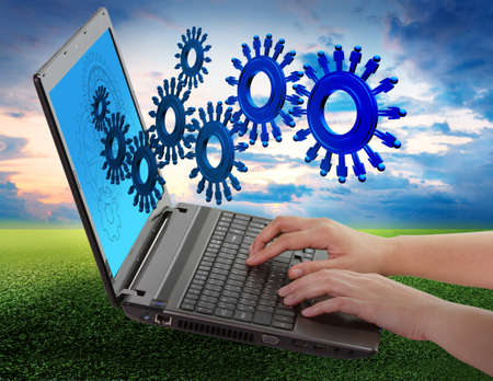 hand using laptop computer and people cogs as concept Stock Photo - 16097366