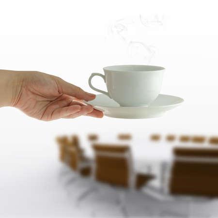 office break: taza de caf� en la mano de la mujer en el fondo reuni�n de la mesa