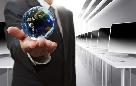 executive job search: Business man hand holds globe and social networkElements of this image furnished by NASA