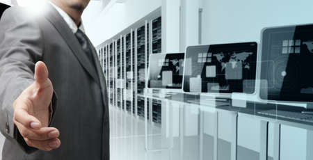 data center data centre: business man offers hand shake in computer center Stock Photo