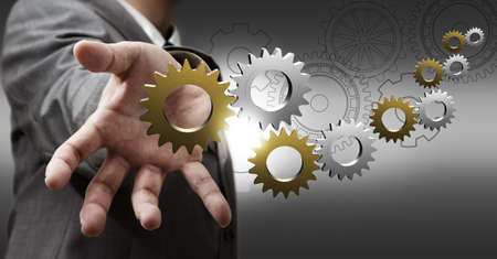 business man hand shows 3d metallic cogs and gears as concept