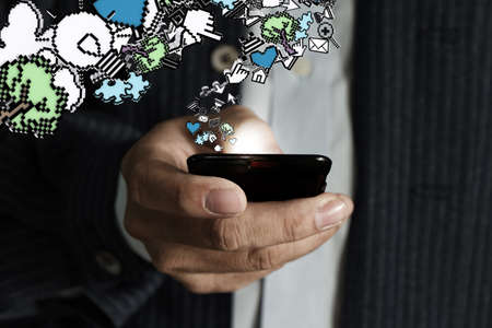 close up of touch screen mobile phone in businessman hand and pixel icons Stock Photo - 16096929
