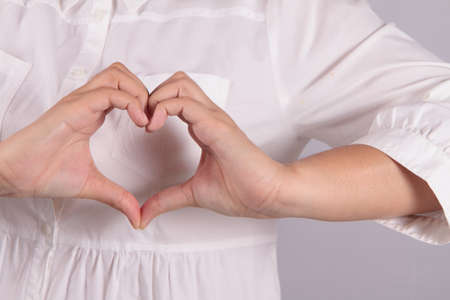 Shape of the heart made by female hands isolated on white photo