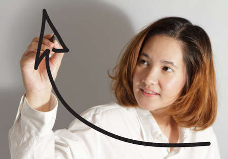 Businesswoman drawing a rising arrow, representing business growth photo