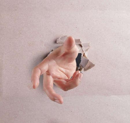 open hand breaking through textured background photo