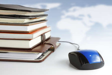 Stack of books and mouse. Online education and business concept. photo